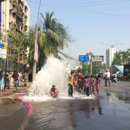路上に突如現れた噴水で、水浴びを楽しむ路上生活者の子どもたち。